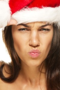 beautiful woman wearing santas hat looking angry on white background